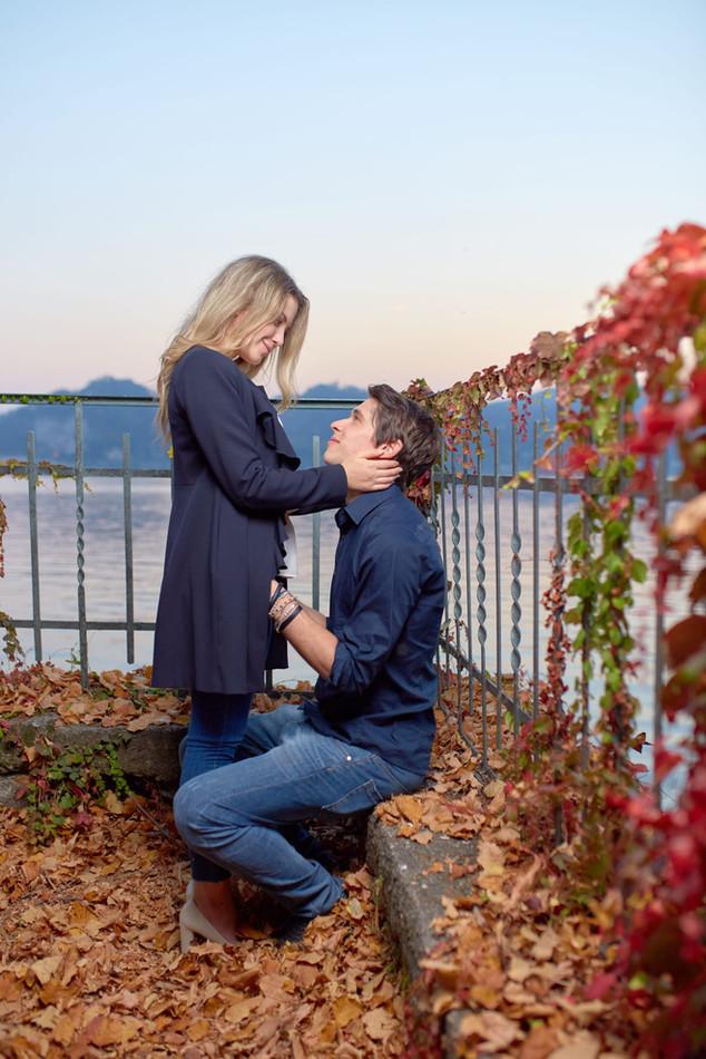Fidanzati innamorati vicino al lago su foglie autunnali servizio di fidanzamento, fotografo di matrimonio