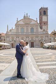 sposi in piazza ducale a Vigevano con chiesa sullo sfondo, figura intera, fotografo matrimonio Novara,