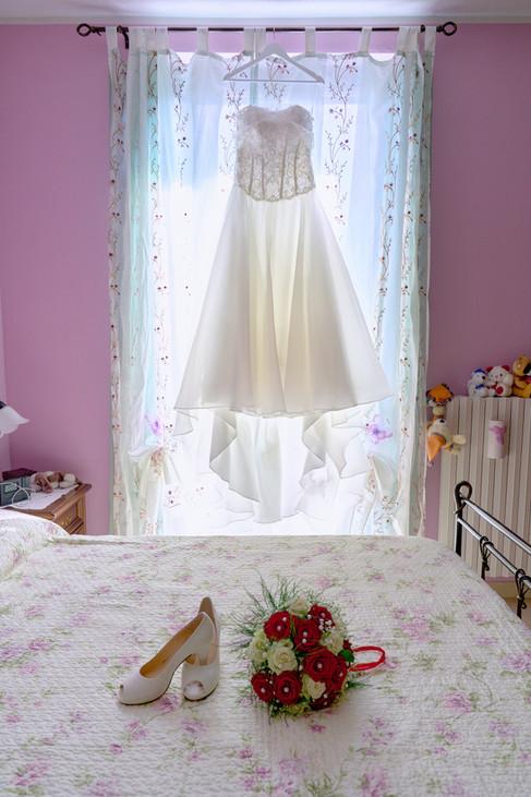 abito da sposa appeso, scarpe e bouquet sul letto, fotografo matrimonio Novara