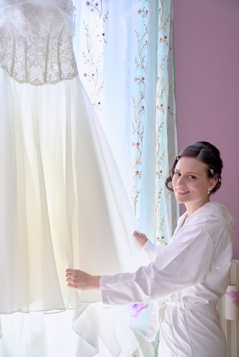 sposa sorridente vicino al vestito, fotografo matrimonio Novara