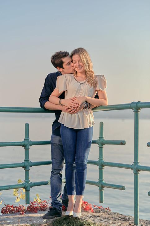 Fidanzati abbracciati in piedi, vicino alla ringhiera e sfondo del lago, servizio di fidanzamento, fotografo di matrimonio