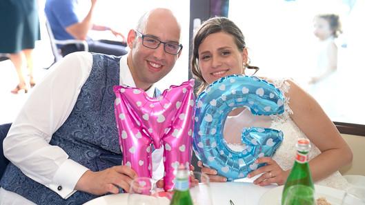sposi felici al tavolo con palloncini a forma di iniziali, fotografo matrimonio Novara,