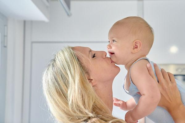 Mamma che solleva e bacia bambino, fotografo battesimo Novara