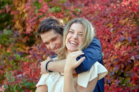Fidanzati abbracciati che ridono, sfondo di foglie autunnali, servizio di fidanzamento, fotografo di matrimonio
