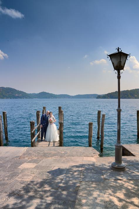 Lampione in primo piano e sposi sul pontile all'isola di San Giulio, fotografo matrimonio Novara,