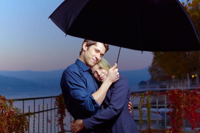 Abbraccio fidanzati di sera su foglie autunnali, servizio di fidanzamento, fotografo di matrimonio