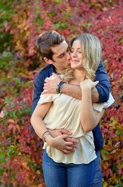 Abbraccio fidanzati innamorati su sfondo di foglie autunnali