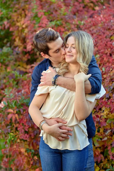 Abbraccio fidanzati innamorati su sfondo di foglie, servizio di fidanzamento, fotografo di matrimonio