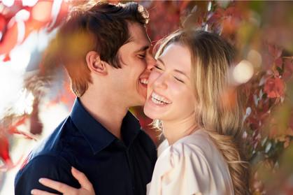 Fidanzati che ridono abbracciati tra le foglie colorate autunnali