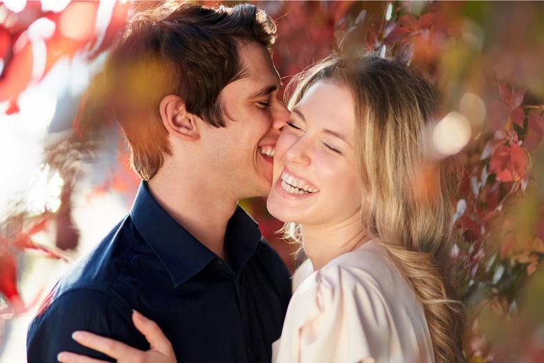idanzati che ridono abbracciati tra le foglie colorate autunnali, servizio di fidanzamento, fotografo di matrimonio