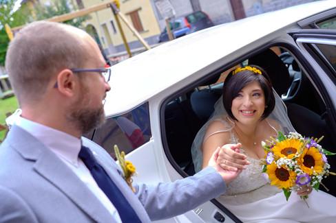 sposa che scende dalla macchina aiutata, fotografo matrimonio Novara