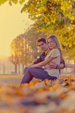 Fidanzati seduti sulle foglie al tramonto con luce dorata