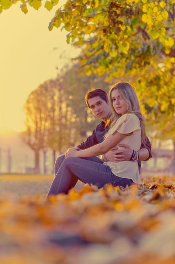 Fidanzati seduti sulle foglie al tramonto con luce dorata, servizio di fidanzamento, fotografo di matrimonio
