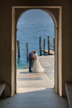 Sposi in riva al lago con quinta di un arco, fotografo matrimonio Novara,