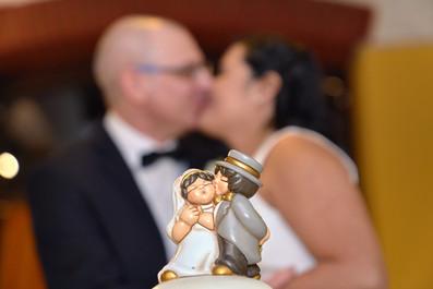 Pupazzetti e decorazioni torta nuziale, bacio degli sposi sfocati sullo sfondo, fotografo matrimonio Novara,
