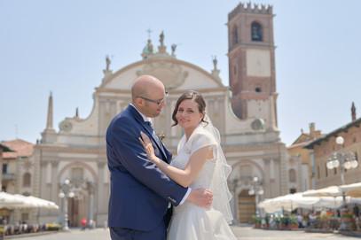 sposi in piazza ducale a Vigevano con chiesa sullo sfondo, mezza figura di profilo, fotografo matrimonio Novara,