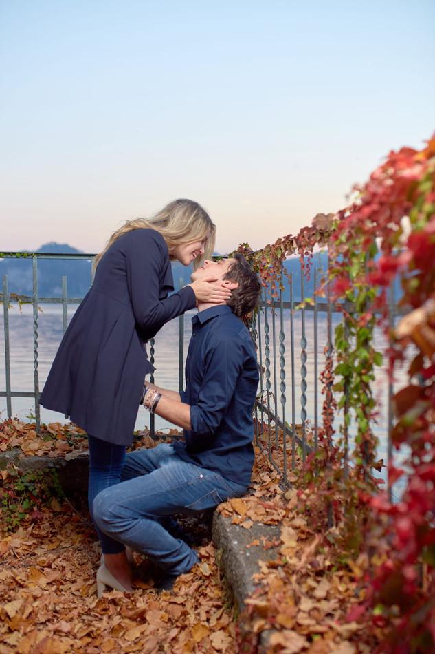 Fidanzati innamorati vicino al lago su foglie autunnali, servizio di fidanzamento, fotografo di matrimonio