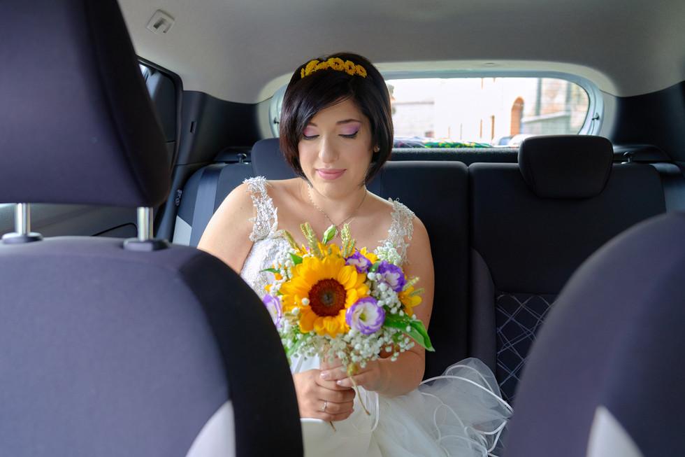 sposa in automobile con bouquet, fotografo matrimonio Novara