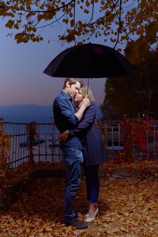 Abbraccio fidanzati di sera su foglie autunnali sotto l'ombrello