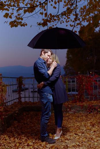 Abbraccio fidanzati di sera su foglie autunnali sotto l'ombrello, servizio di fidanzamento, fotografo di matrimonio