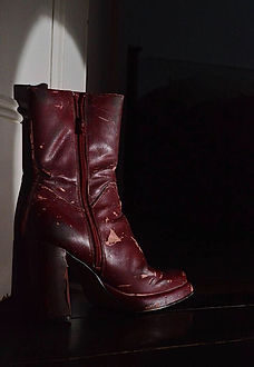 Image of the Red vintage boots discussed in this editorial, looking worn-in with cracked leather. Image is on a black background with a shadow cast on the boots