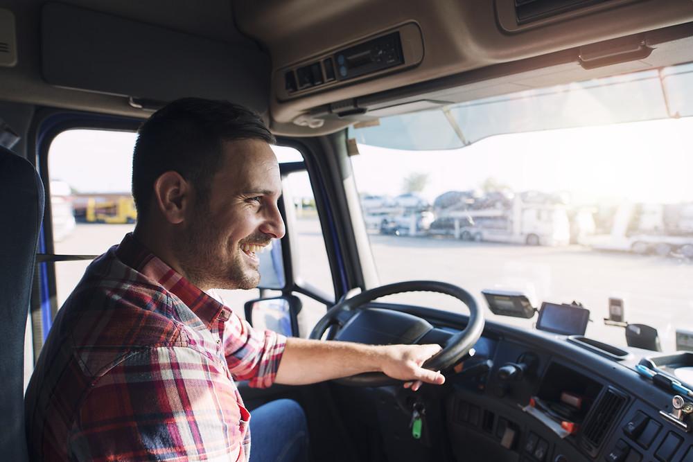 Glücklicher Lastwagenfahrer, der mit breitem Lächeln in der Führerkabine sitzt.