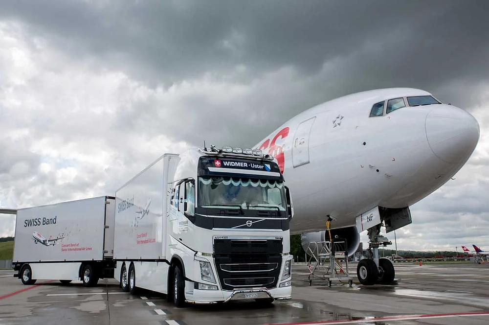 Lastwagen von Widmer Logistics vor einem Swiss Flugzeug.