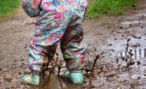 Child splashing puddle
