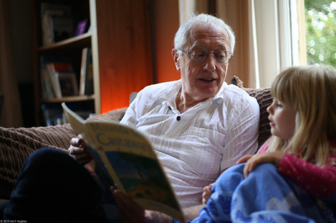 Grandfather reading to child