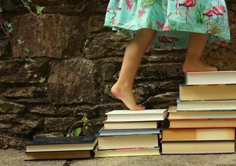 Child climbing steps of books