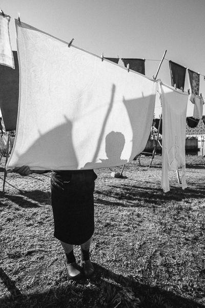 Alte Frau hinter aufgehängter Wäsche