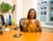 woman-holding-white-ceramic-mug-at-desk-
