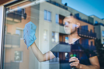 man-cleaning-window-at-home-SX67ZUN copy