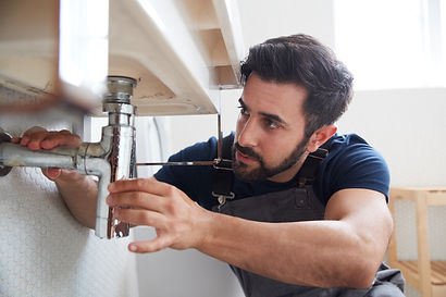 male-plumber-working-to-fix-leaking-sink