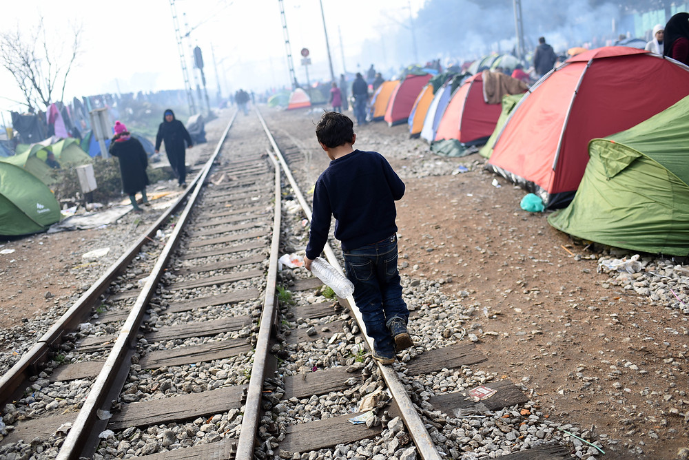 A boy walks through a refugee camp in Greece, 2015 ©UNICEF/UN012790/Georgiev