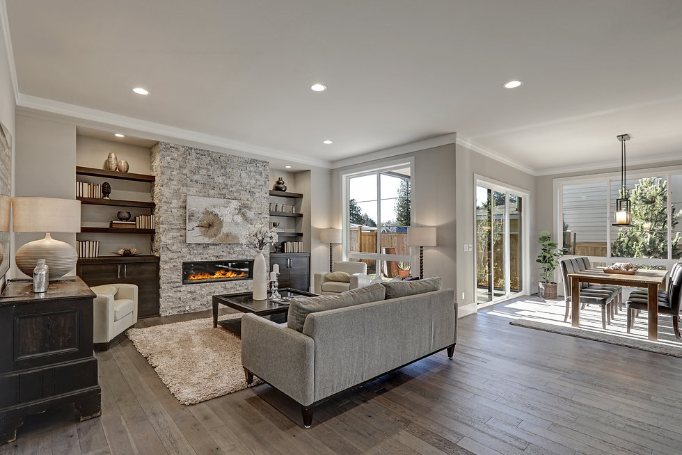 Living room interior in gray and brown colors features gray sofa atop dark hardwood floors