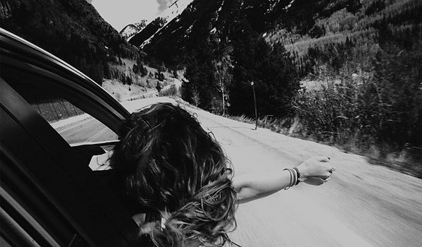 Free-spirited young female traveler extends body outside car window driving through Rocky Mountain National Park