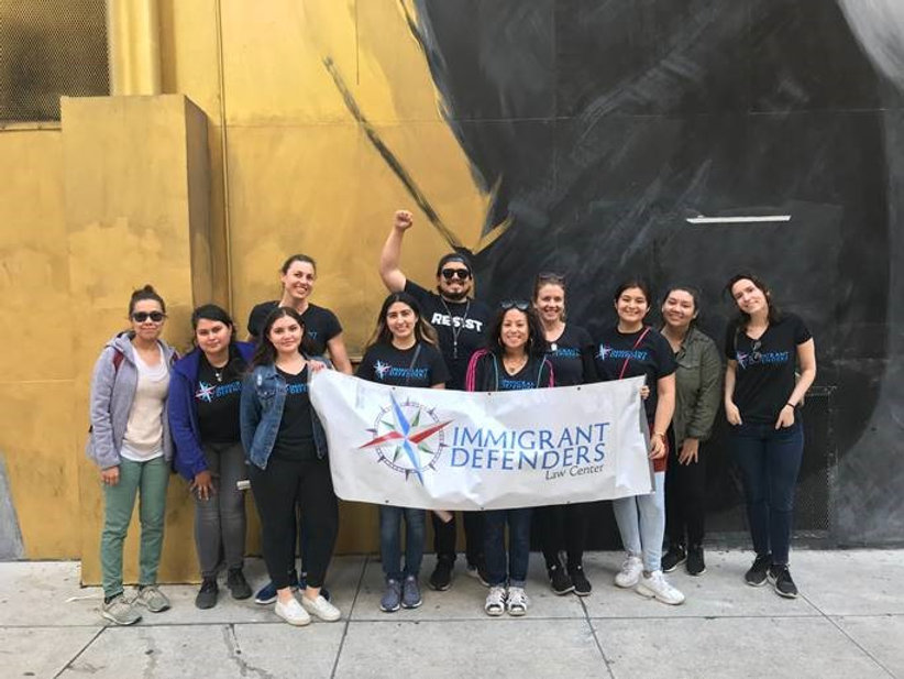 Immigrant Defenders Law Center staff hold up banner and raise their fist in group photo