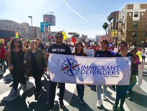 Immigrant Defenders Law Center staff march at a protest, smiling and holding a banner.