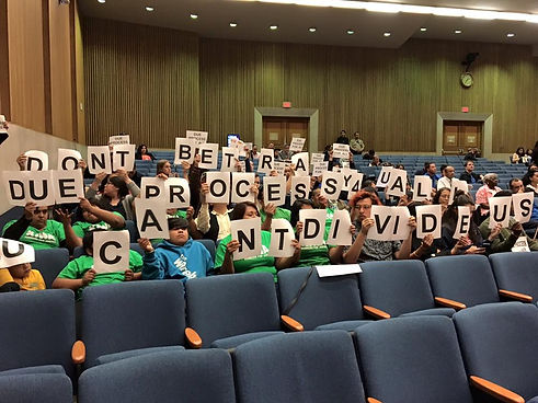 """LAJF supporters attend council meeting and hold up signs that read """"DON'T BETRAY DYE PROCESS - CANT DIVIDE US"""""""