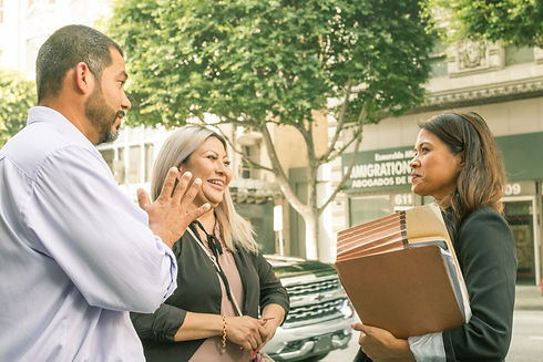 Clients, a man and a woman, smile at their attorney