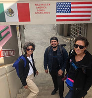 "Staff members Susan Alva, Lisa Okamoto, and Jonathan Barrales stand under Mexican and United States flags with the words, ""Nacimos en America, somos Americanos"""