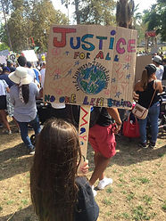 """A little girl holds a sign at a protest that reads """"JUSTICE FOR ALL -  NO ONE LEFT BEHIND"""""""