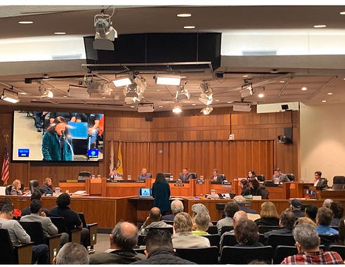 Immigrant Defenders Law Center Staff member presenting at Santa Ana City Council meeting in support of the Santa Ana Justice Fund.