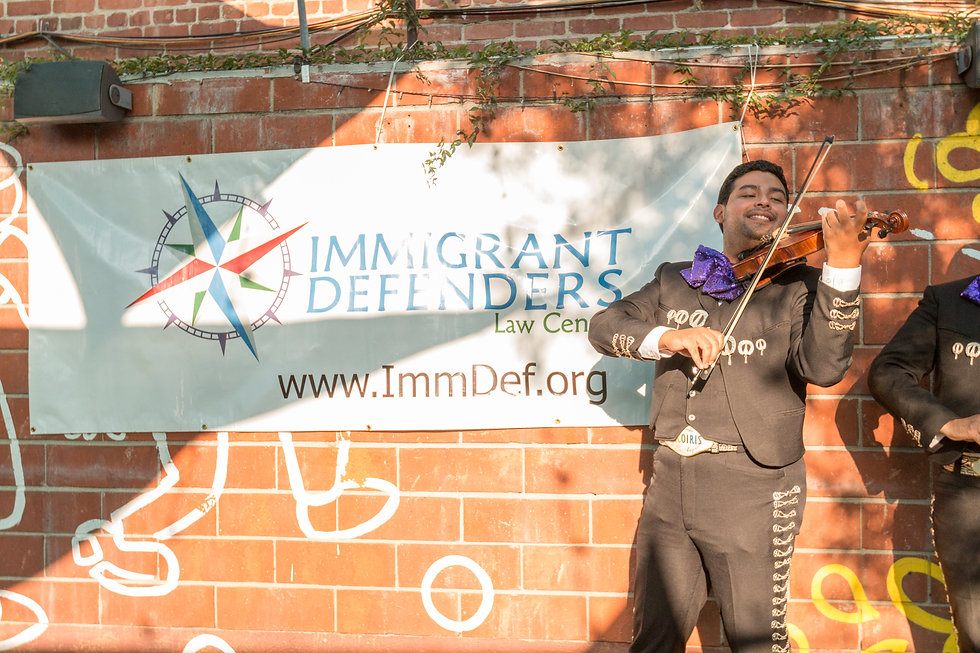 """A mariachi band plays as large banner reads """"Immigrant Defenders Law Center"""" behind them."""