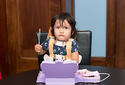 Immigrant Defenders Law center child client holds pen while playing with toys.