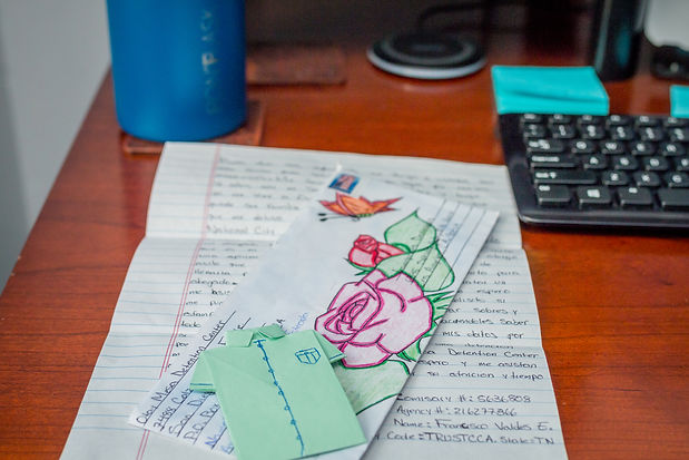 A beautifully drawn rose and butterfly atop an envelope for a thank you letter received from a detained client.
