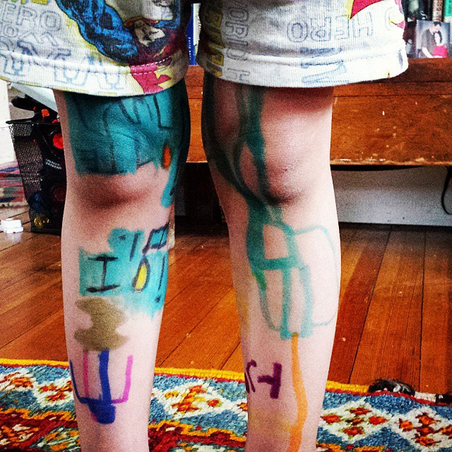 a toddler's legs have images, letters, and colors drawn on them; superhero shorts show the words HERO and a bit of a flying Superman