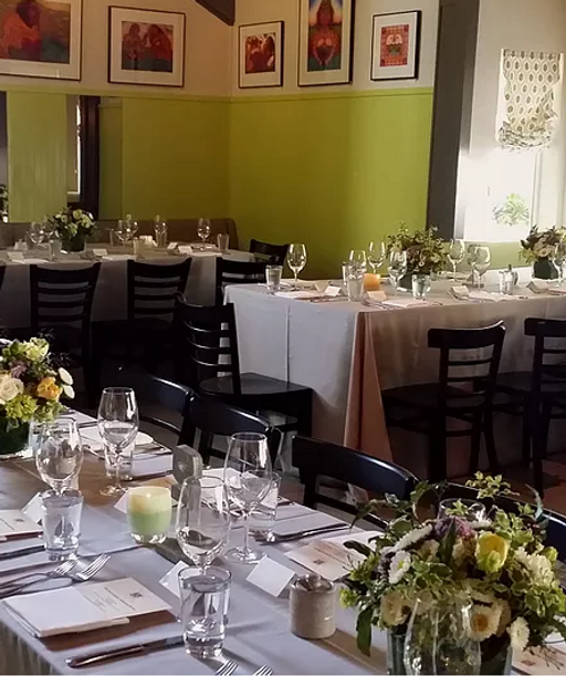 the cafe interior with private event st up with table cloths and floral arrangements