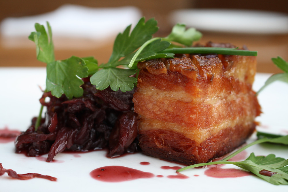 crispy pork belly red wine braised cabbage, picked herbs